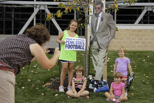 Photo -   FILE - This Aug. 31, 2012 file photo shows Sarah Brown, left, of Kutztown, Pa., taking a picture of her children, from left, Molly, Caroline, Susanna, and Eloise next to a cardboard cutout of former Penn State head football coach Joe Paterno, outside Beaver Stadium on Penn State's main campus in State College, Pa. The bronzed statue outside Beaver Stadium is gone. The record of 409 career victories erased by the NCAA. But reminders of the late coach Paterno still abound on Penn State football game days. (AP Photo/Gene J. Puskar, File)