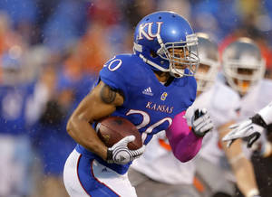 Photo - Kansas' D.J. Beshears (20) rushes during the college football game between Oklahoma State University (OSU) and the University of Kansas (KU) at Memorial Stadium in Lawrence, Kan., Saturday, Oct. 13, 2012. Photo by Sarah Phipps, The Oklahoman