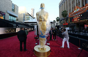 Photo - A statue in the likeness of an Oscar award is displayed on the red carpet for the 85th Academy Awards in Los Angeles, Saturday, Feb. 23, 2013. The Academy Awards are scheduled for Sunday, Feb. 24, 2013. (Photo by Matt Sayles/Invision/AP)