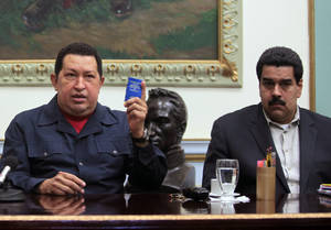 "photo - FILE - In this Dec. 8, 2012, file photo released by Miraflores Press Office, Venezuela's President Hugo Chavez, left, holds up a copy of the Venezuelan national constitution as his Vice President Nicolas Maduro looks on during a televised speech at Miraflores presidential palace in Caracas, Venezuela. Chavez has suffered ""new complications"" following his cancer surgery in Cuba, Maduro said Sunday, Dec. 30, 2012, describing the Venezuelan leader's condition as delicate. (AP Photo/Miraflores Press Office, Marcelo Garcia, file)"