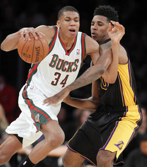 Photo - Milwaukee Bucks guard Giannis Antetokounmpo (34) drives around Los Angeles Lakers forward Nick Young during the first half of an NBA basketball game Tuesday, Dec. 31, 2013, in Los Angeles. (AP Photo/Alex Gallardo)
