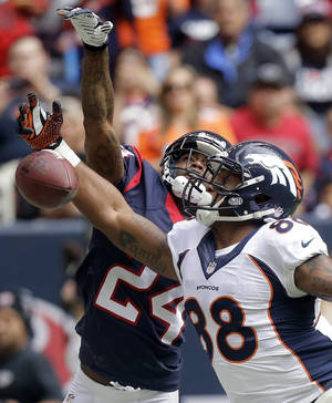Photo - Houston Texans' Johnathan Joseph (24) breaks up a pass intended for Denver Broncos' Demaryius Thomas (88) during the first quarter of an NFL football game on Sunday, Dec. 22, 2013, in Houston. (AP Photo/Patric Schneider)