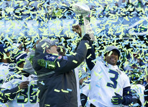 Photo - Seattle Seahawks owner Paul Allen, left, lifts the Vince Lombardi Trophy with Seahawks quarterback Russell Wilson (3) during a rally on Wednesday, Feb. 5, 2014, in Seattle. The Seahawks defeated the Denver Broncos on Sunday in NFL football's Super Bowl XLVIII game in East Rutherford, N.J. (AP Photo/Ted S. Warren)