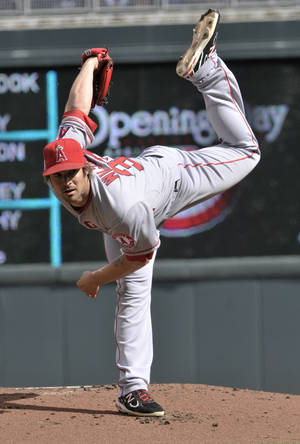 Photo -   Los Angeles Angels pitcher C.J. Wilson follows through on a pitch against the Minnesota Twins in the first inning of a major league baseball game Monday, April 9, 2012, in Minneapolis. (AP Photo/ Jim Mone)