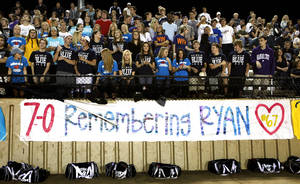 Photo - Edmond North fans stand behind a banner honoring player Ruan Smith (67) as the Westmoore Jaguars play the Edmond North Huskies at Moore Stadium on Friday, Oct. 14, 2011, in Moore, Okla.   Photo by Steve Sisney, The Oklahoman