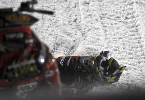 Photo - In this photo taken Jan. 24, 2013, Caleb Moore lies in the snow after he crashed during the snowmoblie freestyle event at the Winter X Games in Aspen, Colo. Moore remains in critical condition in a Colorado hospital after this dramatic crash. A family spokeswoman reissued a statement Tuesday, Jan. 29, 2013, thanking fans, friends and family for their support and asked for continued prayers. They declined further comment. (AP Photo/The Colorado Springs Gazette, Christian Murdock) MAGS OUT