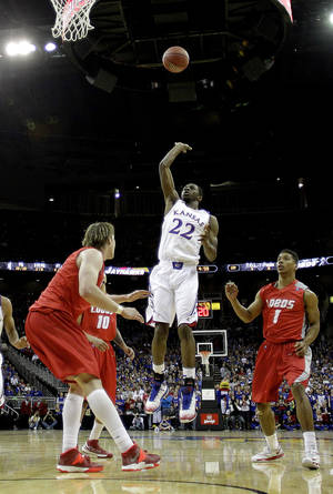 Photo - Kansas' Andrew Wiggins (22) puts up a shot between New Mexico's Cleveland Thomas (1) and Cameron Bairstow, left, during the first half of an NCAA college basketball game Saturday, Dec. 14, 2013, in Kansas City, Mo. (AP Photo/Charlie Riedel)