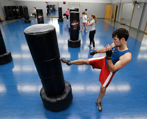 Photo - Michael Purdy, of Edmond, works out Tuesday on the campus of the University of Oklahoma.
