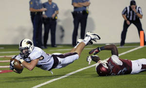 Photo -   Louisiana Monroe wide receiver Brent Leonard, left, dives past Arkansas safety Rohan Gaines for a 23-yard touchdown with 47 seconds left in regulation to send the game into overtime in an NCAA college football game in Little Rock, Ark., Saturday, Sept. 8, 2012. Louisiana-Monroe defeated Arkansas 34-31 in overtime. (AP Photo/David Quinn)