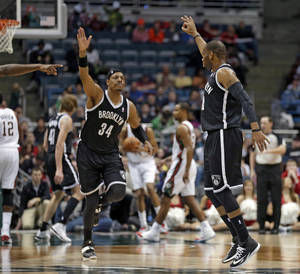 Photo - Brooklyn Nets' Marcus Thornton, right, and teammate Paul Pierce (34) celebrate Thornton's 3-point basket against the Milwaukee Bucks in the second half of an NBA basketball game Saturday, March 1, 2014, in Milwaukee. (AP Photo/Jeffrey Phelps)