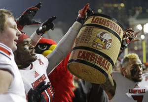 Photo - Louisville players hoist the Keg of Nails after they defeated Cincinnati 31-24 in overtime of an NCAA college football game on Thursday, Dec. 5, 2013, in Cincinnati. (AP Photo/Al Behrman)