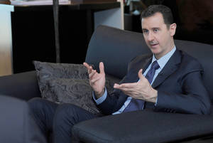 Photo - FILE - In this Monday, Aug. 26, 2013 file photo released by the Syrian official news agency SANA, Syrian President Bashar Assad gestures as he speaks during an interview with a Russian newspaper, in Damascus, Syria. As the Obama administration tries to prod Congress into backing armed action against Syria, the regime in Damascus is hiding military hardware and shifting troops out of bases into civilian areas. (AP Photo/SANA, File)