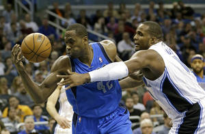 photo - Dallas Mavericks' Elton Brand, left, goes after a loose ball next to Orlando Magic's Glen Davis, right, during the first half of an NBA basketball game, Sunday, Jan. 20, 2013, in Orlando, Fla. (AP Photo/John Raoux)
