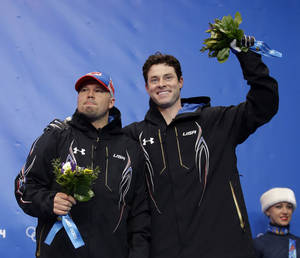 Photo - The team from the United States USA-1, piloted by Steven Holcomb and brakeman Steven Langton, celebrate their bronze medal win after the men's two-man bobsled competition at the 2014 Winter Olympics, Monday, Feb. 17, 2014, in Krasnaya Polyana, Russia. (AP Photo/Dita Alangkara)