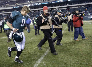 Photo - Philadelphia Eagles' Nick Foles, left, runs off the field after the Eagles lost an NFL wild-card playoff football game against the New Orleans Saints, 26-24, Saturday, Jan. 4, 2014, in Philadelphia. (AP Photo/Julio Cortez)