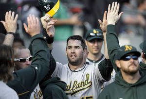 Photo -   Oakland Athletics' Seth Smith is congratulated in the dugout after scoring on an RBI double by Josh Donaldson during the ninth inning of a baseball game against the Detroit Tigers, Thursday, Sept. 20, 2012, in Detroit. (AP Photo/Paul Sancya)