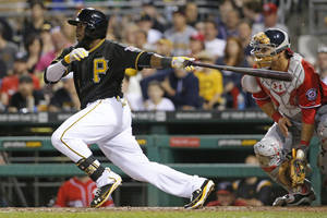 Photo - Pittsburgh Pirates' Josh Harrison, left, drives in the go-ahead run with a single off Washington Nationals starting pitcher Stephen Strasburg during the seventh inning of a baseball game in Pittsburgh, Saturday, May 24, 2014. (AP Photo/Gene J. Puskar)