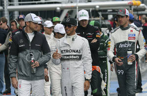 Photo - McLaren driver Jenson Button of Britain, left, and Mercedes driver Lewis Hamilton also of Britain chat as they walk along the pit lane during the Australian Formula One Grand Prix at Albert Park in Melbourne, Australia, Sunday, March 16, 2014. (AP Photo/Rob Griffith)