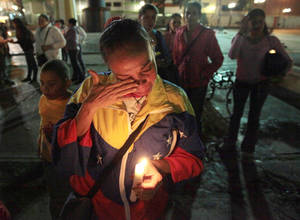 photo - A woman holds a candle as she reacts during a vigil in support of Venezuela's President Hugo Chavez in Caracas, Venezuela, Thursday, Dec. 13, 2012. Chavez is recovering favorably despite suffering complications during cancer surgery in Cuba, his vice president Nicolas Maduro said Thursday amid uncertainty over the Venezuelan leader's health crisis and the country's political future. (AP Photo/Fernando Llano)
