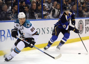 Photo - St. Louis Blues' Alex Pietrangelo (27) gets the puck behind San Jose Sharks' Ryane Clowe (29) in the first period of an NHL hockey game, Tuesday, Feb. 19, 2013, in St. Louis. (AP Photo/Bill Boyce)