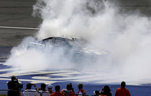 Photo - Driver Jimmie Johnson burns rubber after winning the NASCAR Quicken Loans 400 series auto race at Michigan International Speedway in Brooklyn, Mich., Sunday, June 15, 2014. (AP Photo/Carlos Osorio)