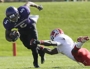Photo -   Northwestern running back Venric Mark (5) is tackled by South Dakota defensive back Chris Frierson (7) during the first half of an NCAA college football game in Evanston, Ill., Saturday, Sept. 22, 2012. Northwestern won 38-7. (AP Photo/Nam Y. Huh)