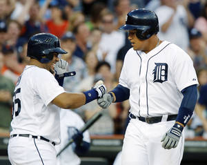 Photo - Detroit Tigers Miguel Cabrera, right, is welcomed at home plate by teammate Brayan Pena after hitting a three-run home run against the Boston Red Sox in the fifth inning of a baseball game on Friday, June 21, 2013, in Detroit. (AP Photo/Duane Burleson)