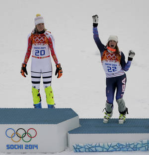 Photo - Women's supercombined bronze medalist United States' Julia Mancuso, right,  celebrates while Germany's gold medalist Maria Hoefl-Riesch, left, waits to take the podium during a flower ceremony at the Alpine ski venue at the Sochi 2014 Winter Olympics, Monday, Feb. 10, 2014, in Krasnaya Polyana, Russia. (AP Photo/Charlie Riedel)