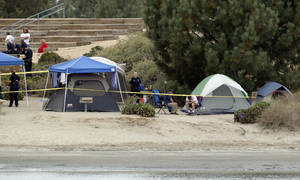 Photo - Crime scene tape surrounds tents and campers at the Boy Scout Summer Camp on Fiesta Island Monday, June 30, 2014, after a boy died from a self-inflicted gunshot wound. The 12-year-old boy died from a gunshot wound to the head Monday morning, and police were investigating whether the shooting was self-inflicted or accidental. (AP Photo/U-T San Diego, John Gibbins)