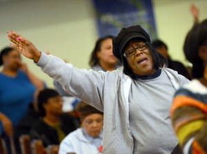 Photo - Barbara Allen raises her hands in prayer during the Concert of Prayer on Tuesday, Jan. 28, 2014, at Word Tabernacle Church in Rocky Mount, N.C. The local church community gathered together after the tragic shooting of four youths behind Word Tabernacle Church on Monday. (AP Photo/The Rocky Mount Telegram, Hannah Potes)
