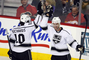 photo - Los Angeles Kings' Jeff Carter, right, high fives teammate Mike Richards after scoring during third period of an NHL hockey action against the Calgary Flames in Calgary, Alberta, Wednesday, Feb. 20, 2013. The Los Angeles Kings beat the Calgary Flames 3-1. (AP Photo/THE CANADIAN PRESS/Jeff McIntosh)