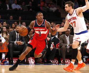Photo - Washington Wizards' Bradley Beal (3) drives against New York Knicks' Andrea Bargnani (77), of Italy, during the second half of an NBA basketball game Monday, Dec. 16, 2013, in New York.  The Wizards won 102-101. (AP Photo/Jason DeCrow)
