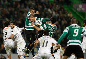 Photo - Sporting's Rojo, from Argentina,  top, jumps for the ball during their Portuguese league soccer match with Academica,  Sunday, Feb. 2 2014, at Sporting's Alvalade stadium in Lisbon. The game ended in a 0-0 draw. (AP Photo/Armando Franca)