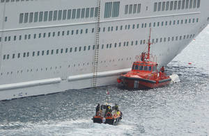 Photo - An orange rescue boat docks by a capsized lifeboat, obscured behind, from the British-operated cruise ship Thomson Majesty in Santa Cruz port of the Canary Island of La Palma, Spain, Sunday Feb. 10, 2013. A lifeboat from the Thomson Majesty fell into the sea at port in Spain's Canary Islands, killing five people and injuring three others Sunday, officials said. Rescue personnel were called to the dockside after a lifeboat with occupants had fallen overboard from a cruise ship. Spanish national broadcaster RTVE said an emergency training drill was taking place at the time of the accident. (AP Photo/Manuel Gonzalez)
