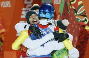 Photo - Germany's Andreas Wank, left, hugs huis teammates after winning the gold during the ski jumping large hill team competition at the 2014 Winter Olympics, Monday, Feb. 17, 2014, in Krasnaya Polyana, Russia. (AP Photo/Dmitry Lovetsky)