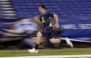 Photo - Texas A&M quarterback Johnny Manziel runs the 40-yard dash at the NFL football scouting combine in Indianapolis, Sunday, Feb. 23, 2014. (AP Photo/Michael Conroy)