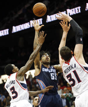 Photo - Charlotte Bobcats guard Chris Douglas-Roberts (55) hits the game-winning shot against Atlanta Hawks Louis Williams (3) and  Mike Muscala (31) as time expires in the second half of an NBA basketball game Monday, April 14, 2014 in Atlanta.  Charlotte won 95-93. (AP Photo/John Bazemore)