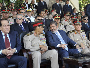 Photo -   In this photo released by the office of the Egyptian Presidency, President Mohammed Morsi, second from right, talks with Field Marshal Hussein Tantawi, second left, as they attend a military graduation ceremony with Prime Minister Kamal el-Ganzouri, left, and Chief of Staff Sami Anan, right, in Cairo, Egypt, Tuesday, July 17, 2012. Egypt's President Mohammed Morsi hailed the Egyptian army and its commanders at a time the newly elected Islamist president and the military council, which took power after ouster of Hosni Mubarak last year, are in mid of power struggle. (AP Photo/Sheriff Abd El Minoem, Egyptian Presidency)