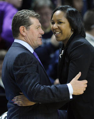 Photo - Connecticut head coach Geno Auriemma, left, greets Temple head coach Tonya Cardoza after Connecticut's 80-36 victory in an NCAA college basketball game in Bridgeport, Conn., Saturday, Jan. 11, 2014. (AP Photo/Fred Beckham)