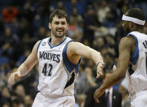 Photo - Minnesota Timberwolves' Kevin Love, left, congratulates Corey Brewer after Brewer's dunk in the first quarter of an NBA basketball game against the Detroit Pistons, Friday, March 7, 2014, in Minneapolis. (AP Photo/Jim Mone)