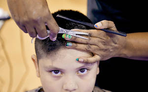 Photo - Adan Ruiz, 8, gets a free back-to-school haircut Monday from Bound4Glory & Beyond at the Boys and Girls Club.  Oklahoma City Public Schools students return to class Wednesday. Photo by Chris Landsberger, The Oklahoman