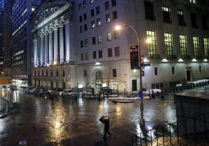 Photo -   Sand bags protect the front of the New York Stock Exchange, Monday, Oct. 29, 2012. Hurricane Sandy continued on its path Monday, forcing the shutdown of mass transit, schools and financial markets, sending coastal residents fleeing, and threatening a dangerous mix of high winds and soaking rain. There had been plans to allow electronic trading to go forward on the New York Stock Exchange but with a storm surge expected to cover parts of lower Manhattan in water, officials decided late Sunday that it was too risky to ask any personnel to staff the exchanges. (AP Photo/Richard Drew)