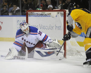 Photo - New York Rangers goaltender Henrik Lundqvist (30), of Sweden, stops Buffalo Sabres center Cody Hodgson, right, during the first period of an NHL hockey game in Buffalo, N.Y., Thursday, Dec. 5, 2013. (AP Photo/Gary Wiepert)