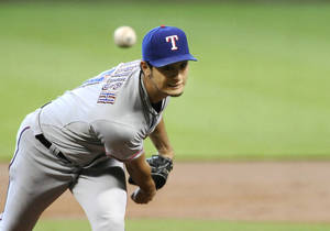 Photo - Texas Rangers' Yu Darvish delivers a pitch against the Houston Astros in the first inning of a baseball game Monday, Aug. 12, 2013, in Houston. (AP Photo/Pat Sullivan)