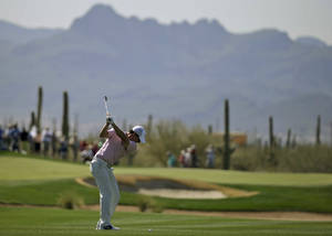 Photo - Rory McIlroy, of Northern Ireland, hits from the fairway on the 17th hole during a practice round for the Match Play Championship golf tournament Tuesday, Feb. 18, 2014, in Marana, Ariz. (AP Photo/Chris Carlson)