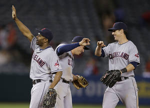 Photo - Cleveland Indians' Michael Bourn, left, Asdrubal Cabrera, center, and Drew Stubbs celebrate their team's 4-1 win against the Los Angeles Angels after a baseball game on Wednesday, Aug. 21, 2013, in Anaheim, Calif. (AP Photo/Jae C. Hong)
