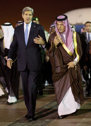Photo - U.S. Secretary of State John Kerry, left,  is escorted by Saudi Foreign Minister Prince Saud Al-Faisal bin Abdulaziz al-Saud, as Kerry arrives in Riyadh, Saudi Arabia, Sunday, Nov. 3, 2013.  (AP Photo / Jason Reed, Pool)