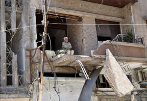 photo -   In this Sunday April 22, 2012 photo, a Syrian man sits on the balcony of his destroyed house damaged from Syrian army forces shelling, at Hamidiyeh neighborhood in Homs province, central Syria. Opposition activists have said observers appear to make a difference in areas where they stay for longer periods, such as the central city of Homs, where a pair of monitors has been deployed since the weekend. Homs had been hammered by regime artillery for weeks, but shelling stopped after the monitors arrived. Gunfights are still reported in some neighborhoods. (AP Photo)