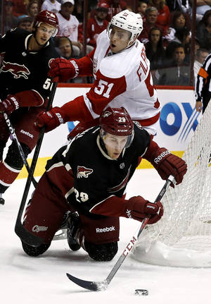 Photo - Detroit Red Wings' Valtteri Filppula (51), of Finland, trips up Phoenix Coyotes' Michael Stone (29) as Coyotes' Antoine Vermette watches in the first period during an NHL hockey game, Monday, March 25, 2013, in Glendale, Ariz. (AP Photo/Ross D. Franklin)