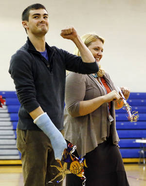 photo - Science teachers Benjamin Cottingham, left, and April Gustafson react during the announcement that Devon Energy gave John Marshall High School its $25,000 Devon Science Giant grant, during an assembly Wednesday at the northwest Oklahoma City school. Cottingham and Gustafson were the ones who applied for the grant. The money will be used to build a Touch Tank interactive marine ecosystems lab. Photo by Nate Billings, The Oklahoman <strong>NATE BILLINGS</strong>